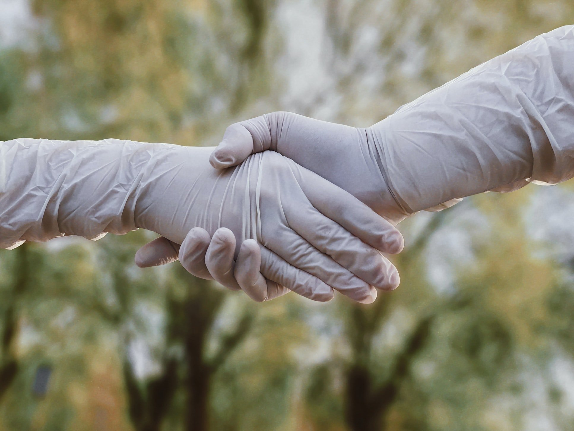 close up of a protected handshake wearing rubber gloves